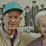 Residents Ralph Ireland and Louise Humphreys pose next to a picture of Charles Lindbergh and Amelia Earhart and recall their memories of flying on airplanes acquired by TWA during World War II.