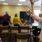 The group does some standing stretches before doing some more seated stretches.