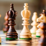 wooden chess pieces on gray background