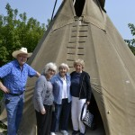 The gang poses for a picture in front of a teepee.