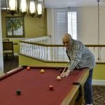 Resident Bob Tice is trying to get a leg-up on his next shot to keep playing for the 9 ball.