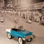 A picture from a peddle car race in Kansas City juxtaposes the car on display to show how much of a part of American culture these childhood toys were!