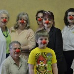 Some residents, associates, and family gathered in our Multi-Purpose Room for a photo of them clowning around for a good cause!