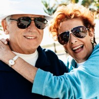 Outdoor Portrait of a Happy Senior Couple Wearing Sunglasses
