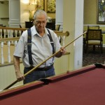 Resident Ralph Ireland is sizing up his next shot in a game of 9-Ball. Don't worry...Ralph sinks the 9!