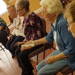 Pictured: (Front-to-Back) Residents Beverly Garvick, Bea Peterson, Ann Pharr, Etta Jane Asher, and Receptionist Stephanie Garland playing Wii Bowling as part of their Watermark University class.