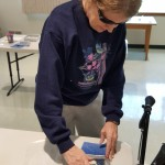 Resident Marianne Schrik making recycled paper on her paper screen.