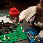 Mary Louise Taylor explores some hands on interaction with the LEGOs in a building area in the exhibit.