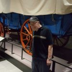 Jim standing next to a wagon model like the ones used on the Santa-Fe Trail during the pioneer westward expansion.