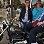 (Left-to-Right): Pat Taylor, Metta Wickham, and Marie Moss pose for a picture with Marie on this slick looking Harley Davidson.